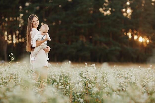 幸せな子供と彼のお母さんは、フィールドで屋外で楽しんでいます。ママは子供を抱きしめ、抱擁します。母の日。セレクティブフォーカス Premium写真