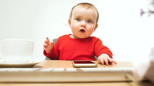 現代のコンピューターのキーボードまたは白いスタジオでラップトップで座っている幸せな子供女の赤ちゃん 無料写真