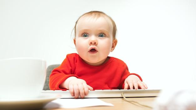 행복 한 아이 아기 소녀 흰색 현대 컴퓨터 또는 노트북의 키보드와 함께 앉아 무료 사진
