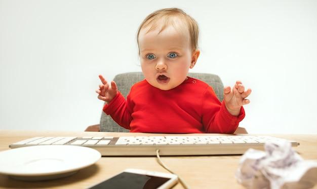 現代のコンピューターまたは白いスタジオで分離されたラップトップのキーボードで座っている幸せな子供女の赤ちゃん 無料写真