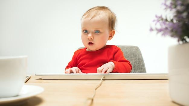 Bambino felice della neonata del bambino che si siede con la tastiera del computer isolata su un bianco Foto Gratuite