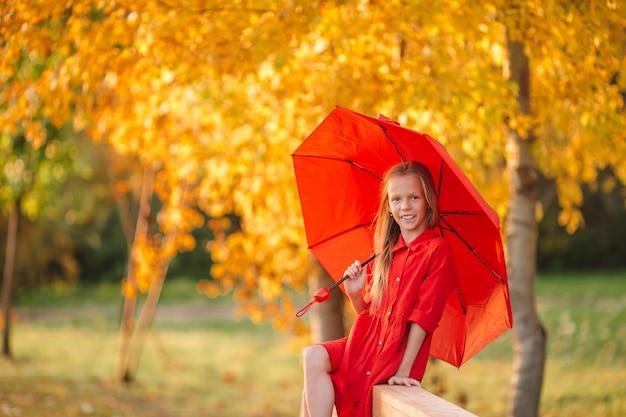 Happy child girl laughs under red umbrella Premium Photo