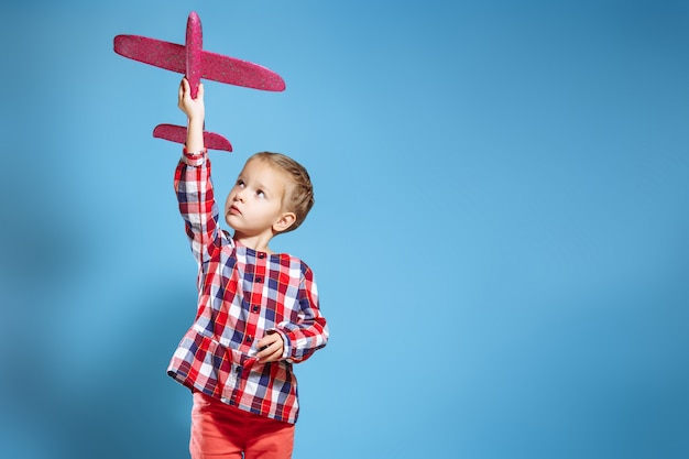 Happy child girl playing with toy airplane. the dream of becoming a pilot. Premium Photo