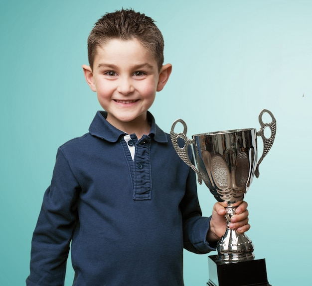 Happy child holding a trophy Free Photo
