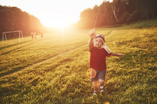 Happy child launch a kite in the field at sunset. little boy and girl on summer vacation Free Photo