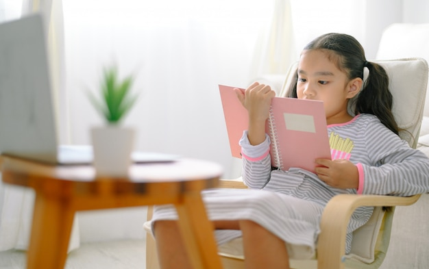 Happy child little asian girl  reading a books on the table in the living room at home, family activity concept Premium Photo