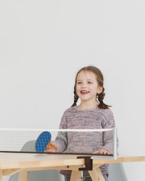 Счастливый ребенок играет в пинг-понг Бесплатные Фотографии