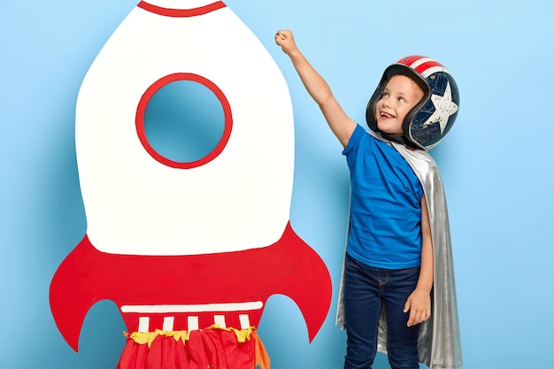 Happy child raises arm near paper carton toy rocket, wants to fly into space Free Photo