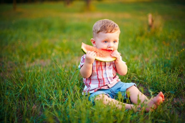 Happy child sitting on green grass and eating watermelon outdoors in spring park against natural Premium Photo