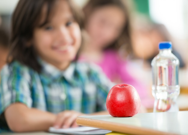 リンゴと水のボトルでclassromに座って笑っている幸せな子供 Premium写真