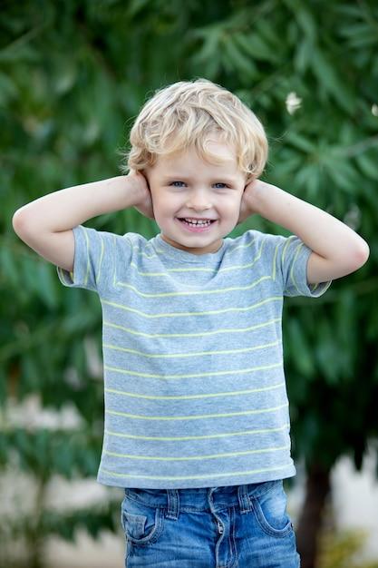 Happy child with blue t-shirt in the garden Premium Photo
