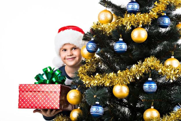 Счастливый ребенок с подарком возле елки Бесплатные Фотографии