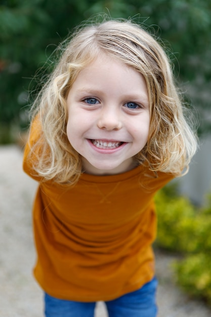 Happy child with red t-shirt in the garden Premium Photo