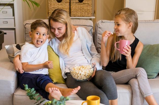Счастливые дети и ее мать едят попкорн Бесплатные Фотографии