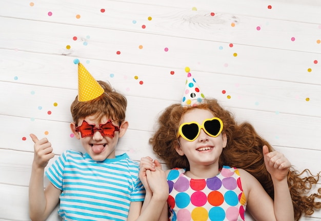Happy children on carnival party, lying on a wooden floor. happy childhood, holiday concept. Premium Photo