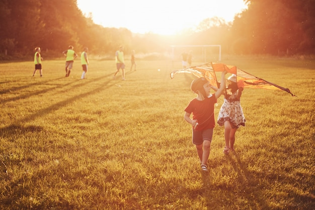 Happy children launch a kite in the field at sunset. little boy and girl on summer vacation Free Photo