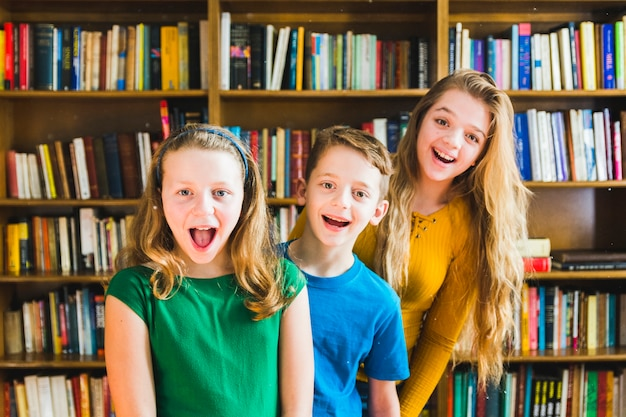 Happy children standing in library  Free Photo