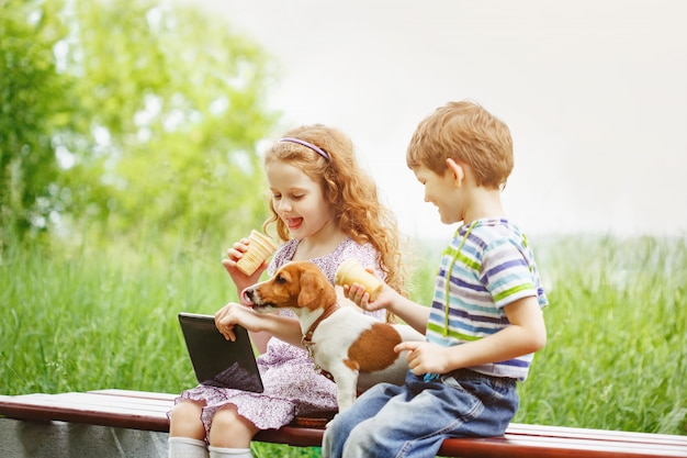 Happy children with a friend puppy dog playing in the tablet pc Premium Photo