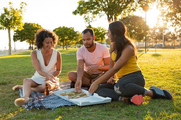 Happy closed friends eating pizza in park Free Photo