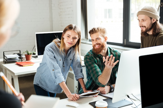 Happy colleagues in office talking with each other Free Photo