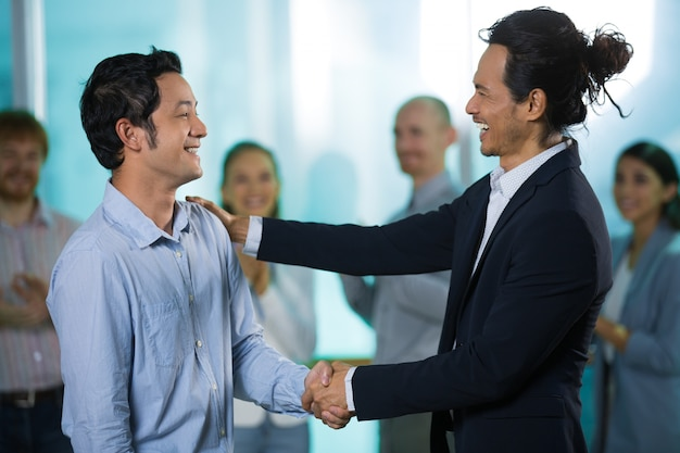 happy colleagues talking while shaking hands photo free download