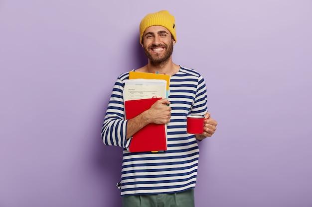 幸せな大学生は、紙とメモ帳を運び、試験の準備をし、カップから温かい飲み物を飲みます 無料写真