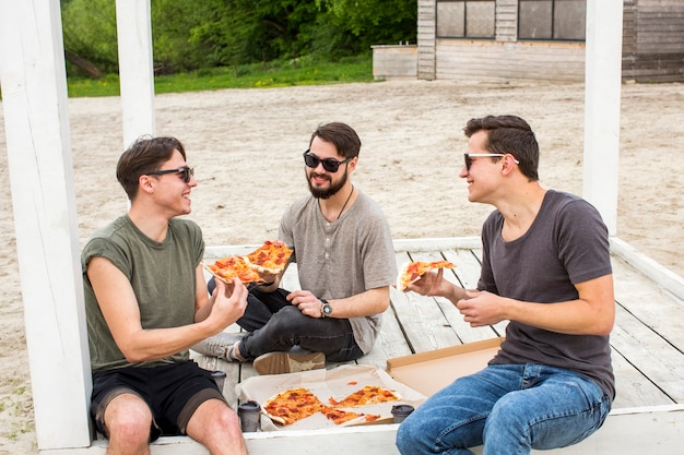 Happy company chatting and eating pizza on picnic Free Photo