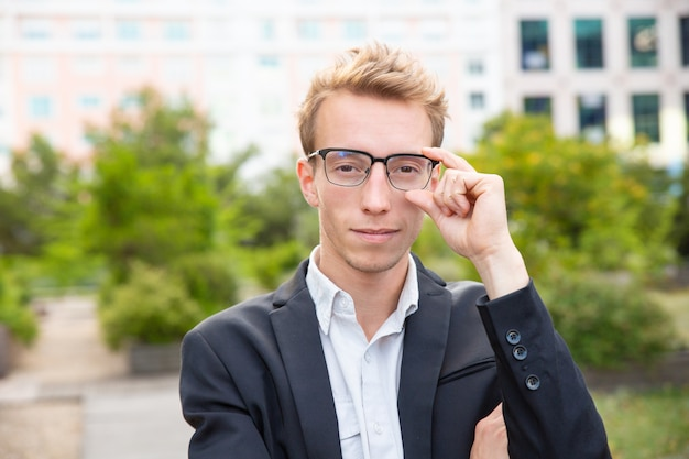 Happy confident businessman in glasses standing for camera Free Photo