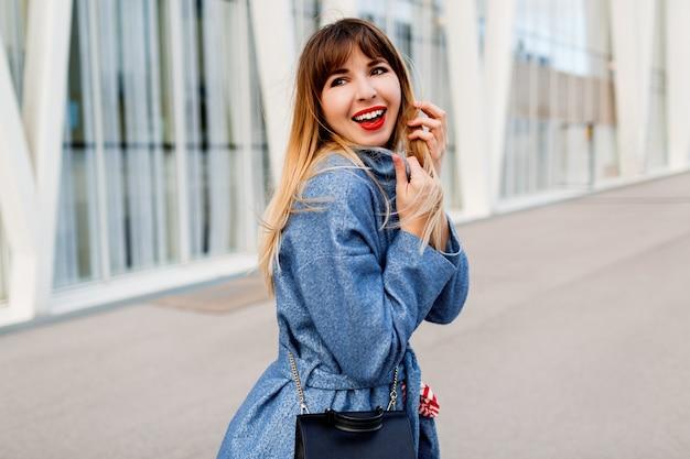 スタイリッシュな青いウールのコートでモダンな通りを歩いて幸せな自信を持って女性 無料写真