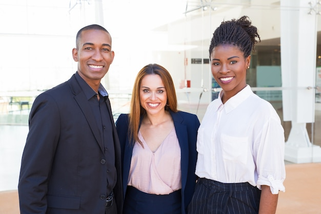 Happy confident young interracial team members embracing Free Photo