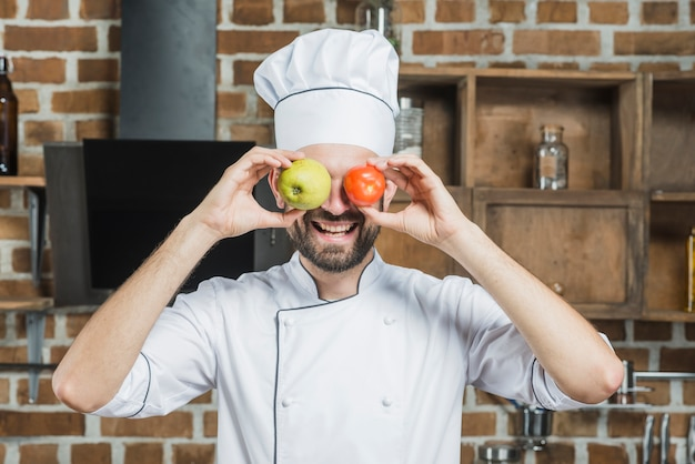 Happy cook holding apple and red tomato in front of his eyes Free Photo