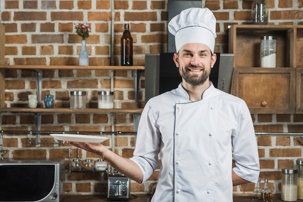 Happy cook wearing chef's hat holding an empty plate in hand Free Photo