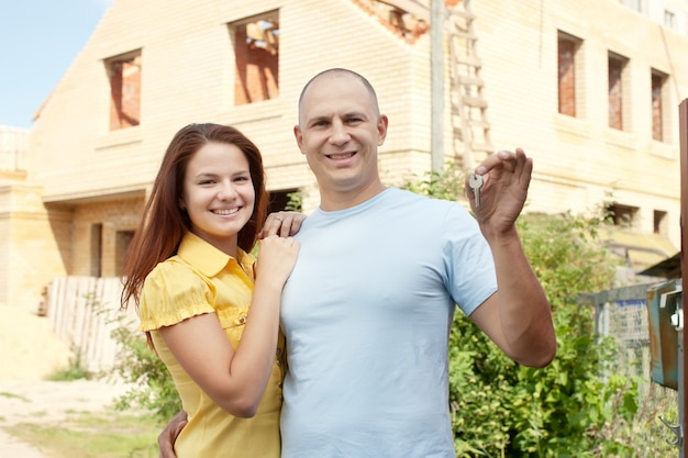 Happy couple against building new house Free Photo