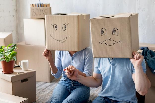 Счастливая пара дома в день переезда с коробками над головами Бесплатные Фотографии