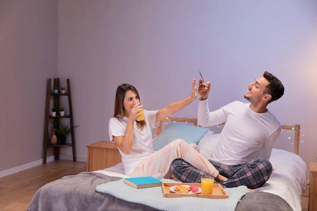 Happy couple in bed taking pictures Free Photo