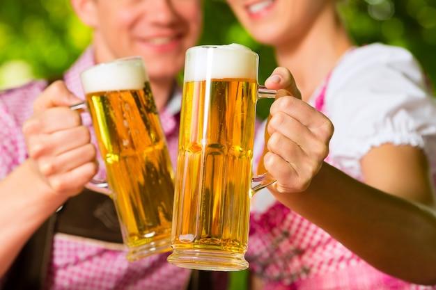 Happy couple in beer garden drinking beer Premium Photo