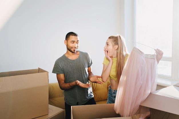 Счастливая пара купила дом, семья переехала в новую квартиру, новоселье, распаковка ящиков. женщина нашла подарок, муж удивил жену, розовую юбку в подарок. мужчина в серой футболке, девушка в желтом топе. Бесплатные Фотографии