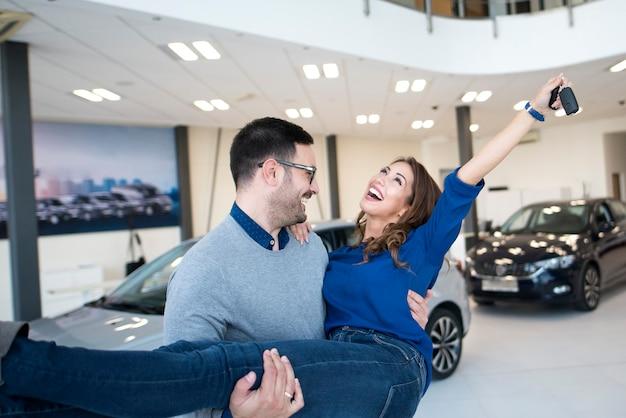 Coppia felice acquisto di auto nuove di zecca presso la concessionaria di veicoli locale Foto Gratuite