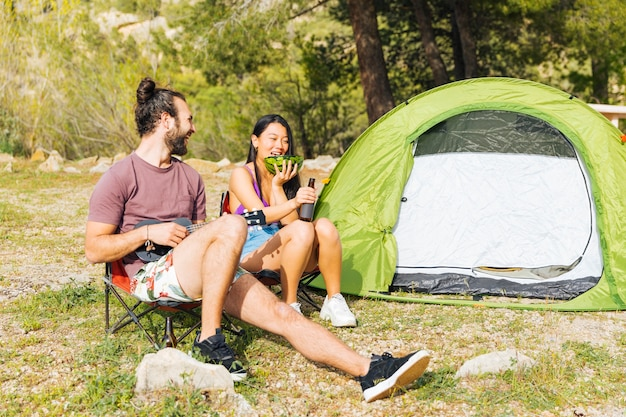 Happy couple camping in forest Free Photo
