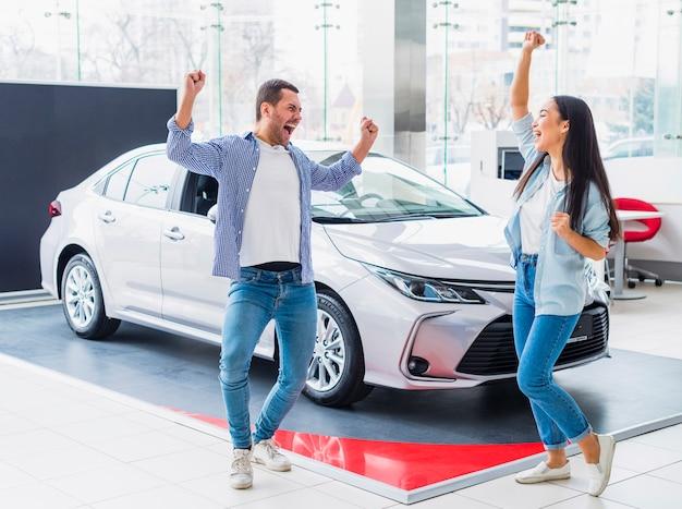 Happy couple at car dealership Free Photo