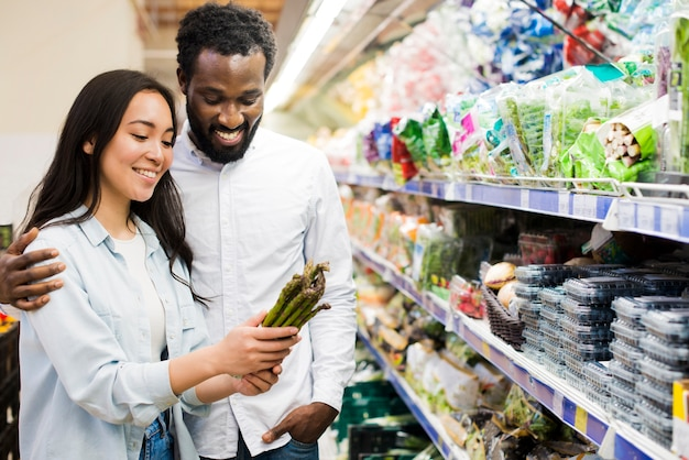 Happy couple choosing asparagus in grocery store Free Photo