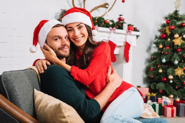 Coppie felici in cappelli di natale che abbracciano sul divano Foto Gratuite