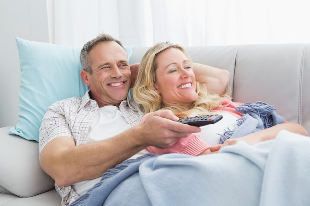 Happy Couple Cuddling On The Couch Watching Television Photo ...