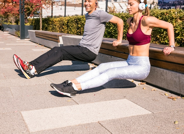 Happy couple doing stretching exercise in the park Free Photo