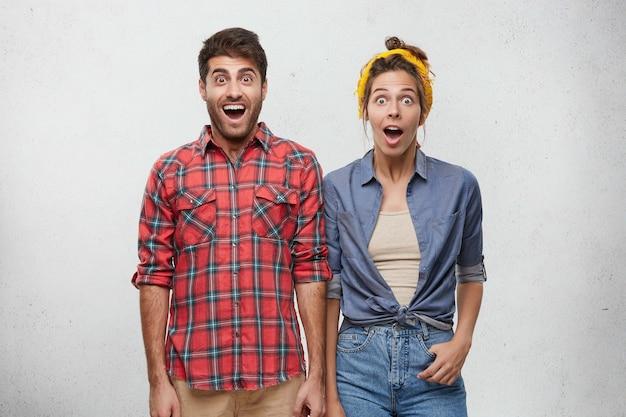 Счастливая пара, одетая небрежно позирует Бесплатные Фотографии
