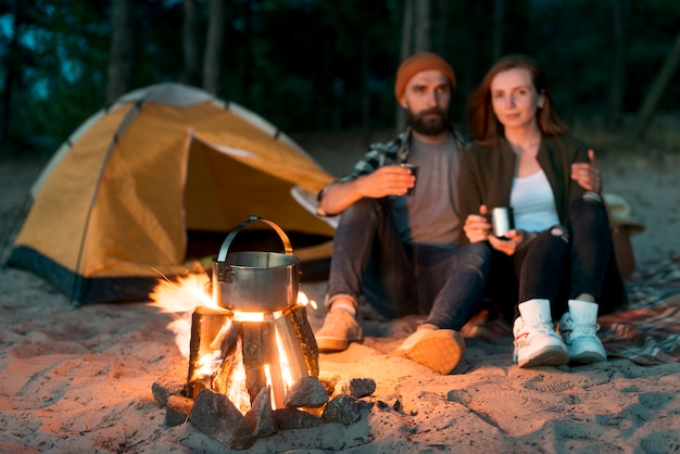 Happy couple drinking together by bonfire Free Photo