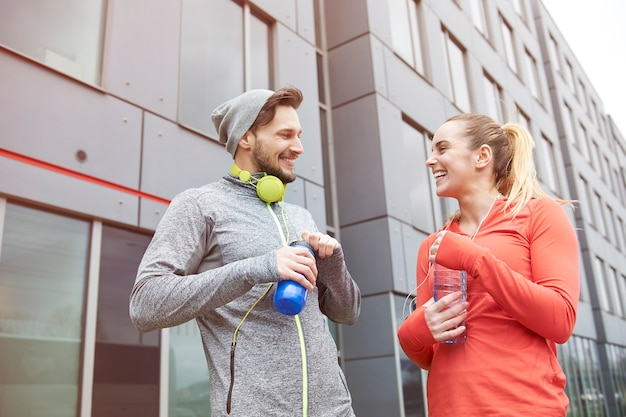 Happy couple drinking water after exercise Free Photo