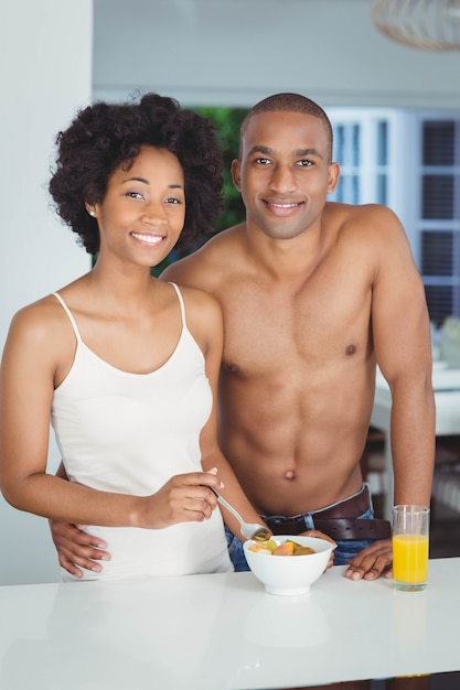 Happy couple eating breakfast in the kitchen at home Premium Photo