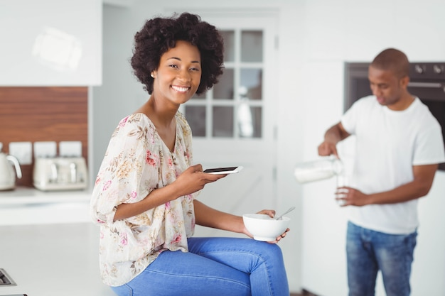 Happy couple eating breakfast and using smartphone in the kitchen at home Premium Photo