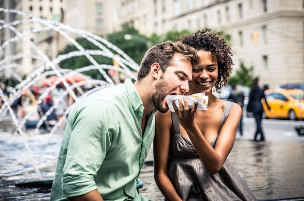 Happy couple eating hot dogs and having fun in new york city Premium Photo